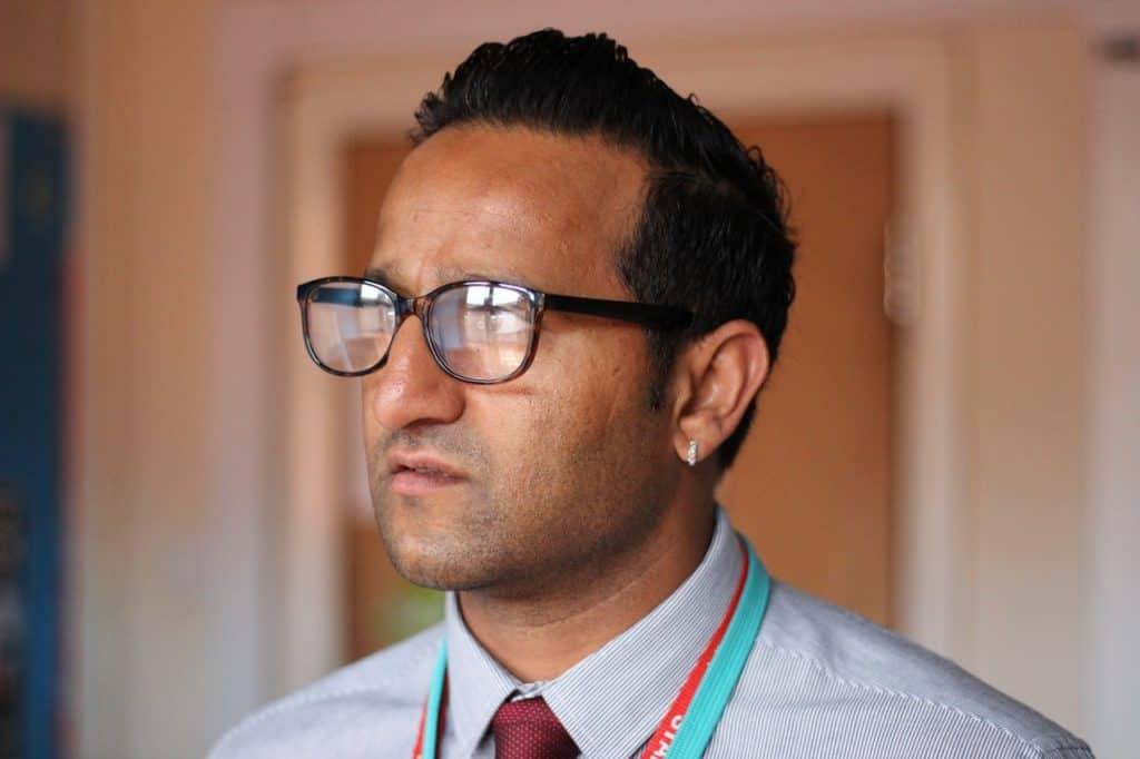 Imagem mostra um homem de óculos, camisa e gravata, usando um pequeno brinco de brilhantes na orelha esquerda.
