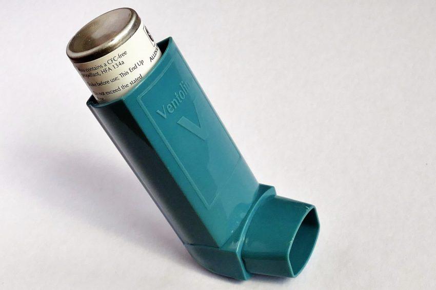 Foto de uma bombinha para asma, de cor verde petróleo, em um fundo branco.