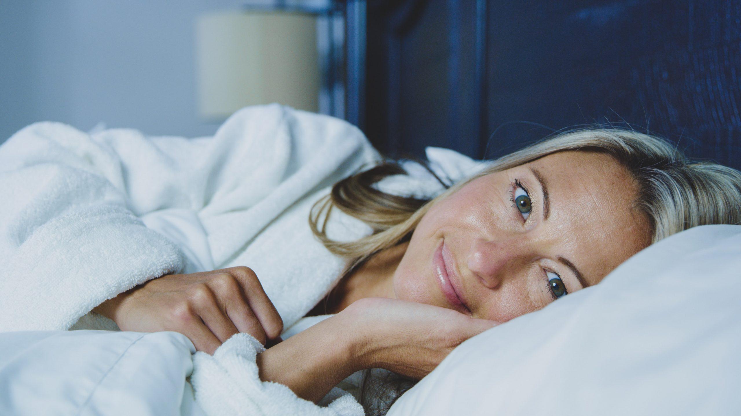 Mulher sorrindo deitada em seu travesseiro de olhos abertos