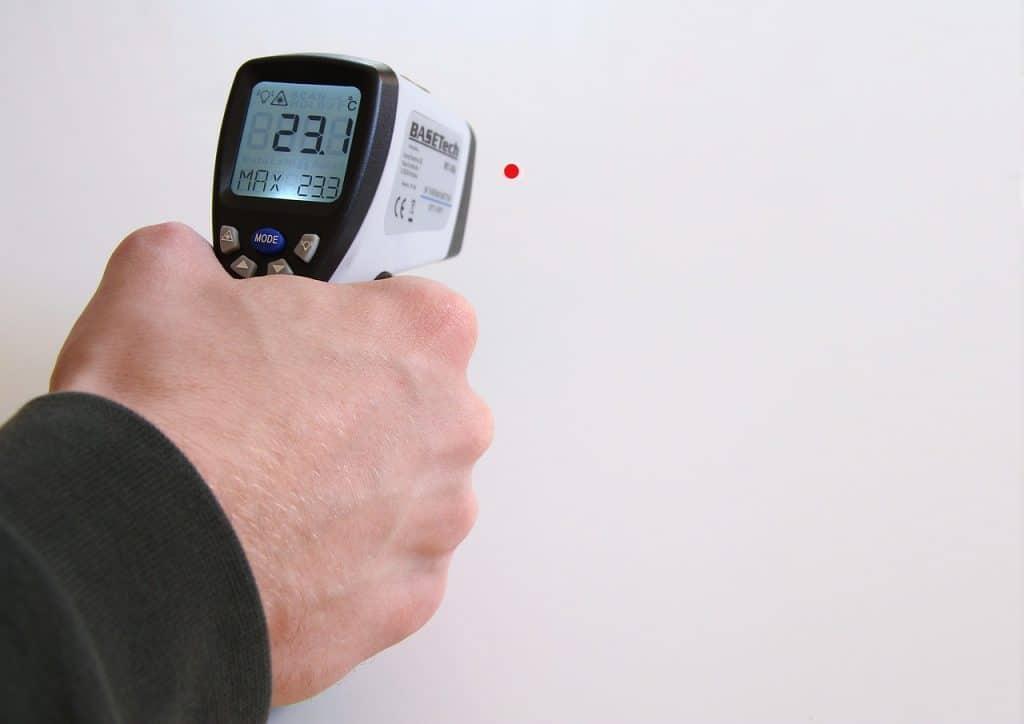 Na foto um homem segurando um termômetro a laser apontado para uma parede.