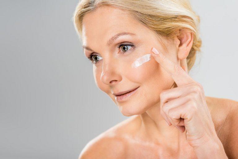 Imagem de uma mulher aplicando hidratante facial.