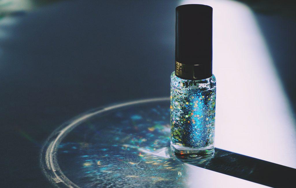 Imagem de um frasco pequeno com líquido brilhante e esverdeado.