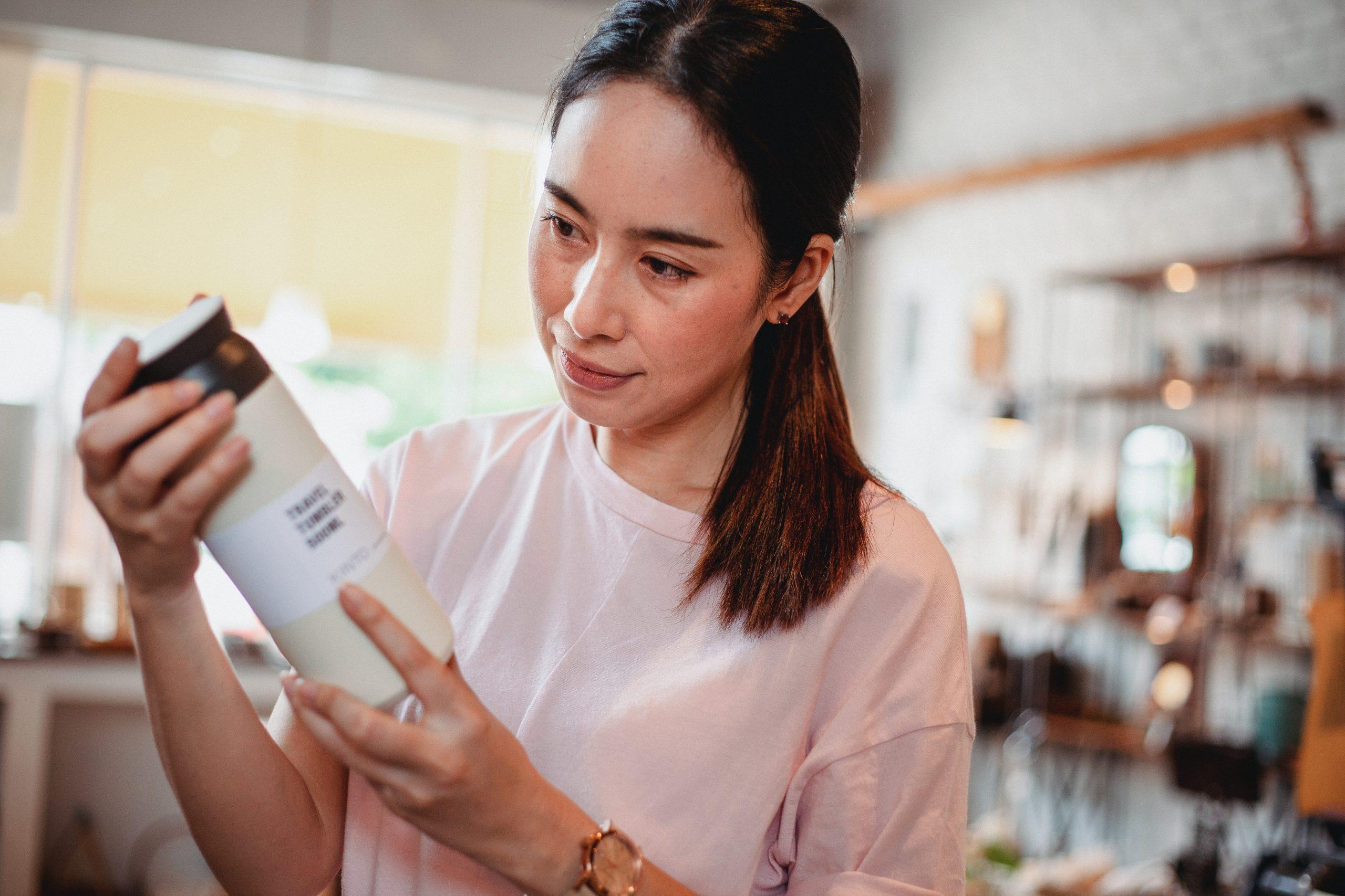 Mulher com frasco na mão lendo o rótulo