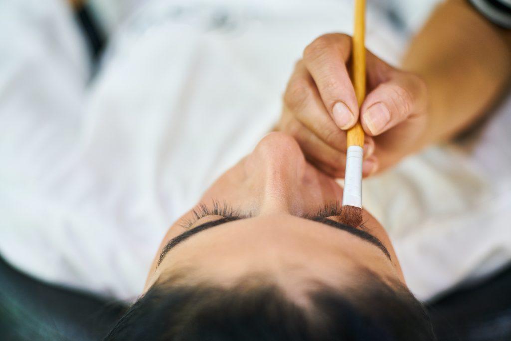 Na foto uma pessoa aplicando um produto na sobrancelha de outra.