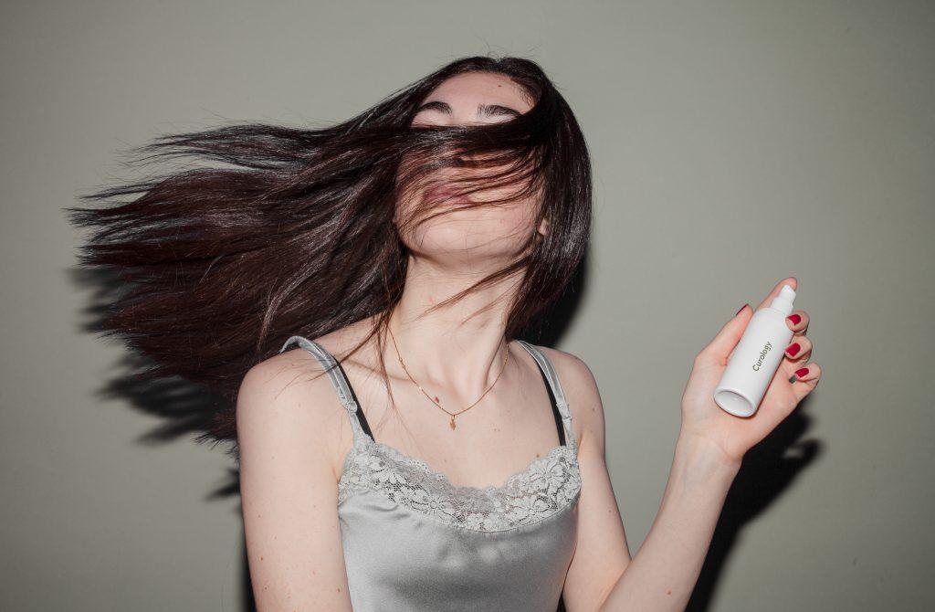 Imagem de uma mulher balançando o cabelo.
