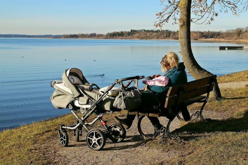 Imagem de uma mulher sentada em um banco de parque com um bebê em seu colo e um carrinho ao seu lado.