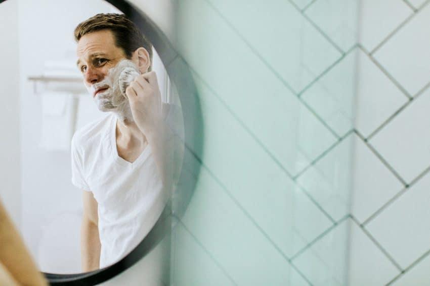Imagem mostra um homem de frente ao espelho, com creme de barbear espalhado pela barba, produzindo espuma com uma escova própria.