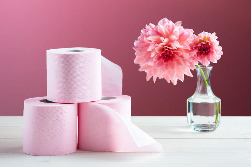Imagem de 3 rolos de papel higiênico rosa com flores ao lado.