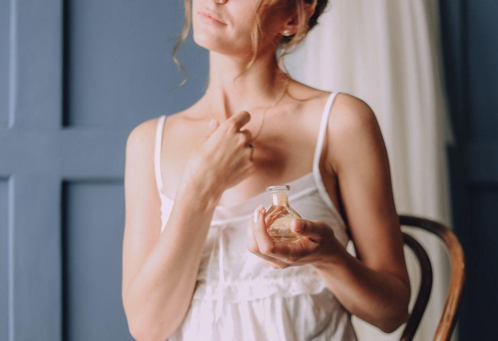 Mulher loira de cabelos presos passa um pouco de perfume em seu colo vestida de pijama branco.