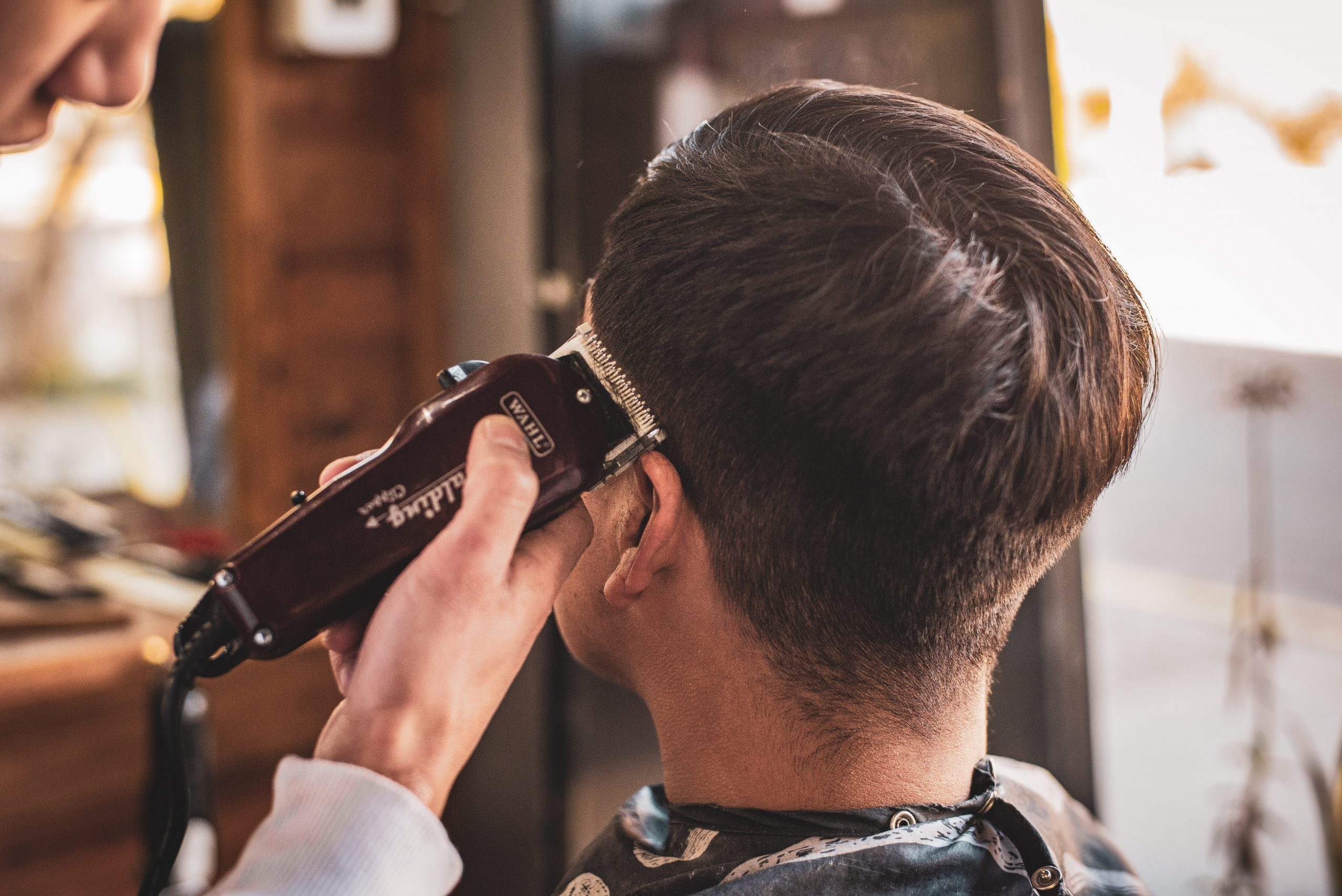 Imagem de um homem cortando o cabelo de um cliente.