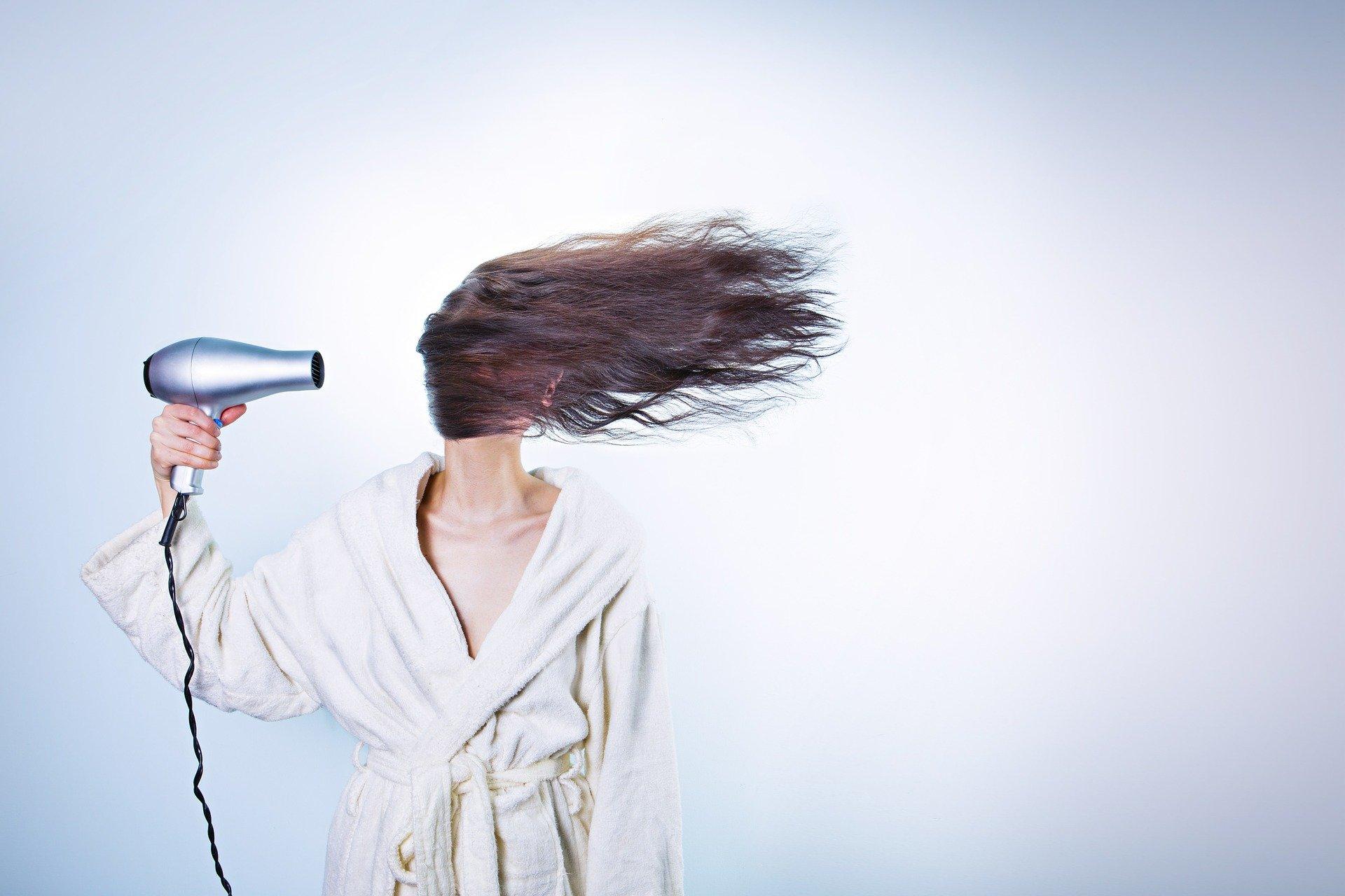 Na foto uma mulher de roupão com um secador de cabelo na mão.