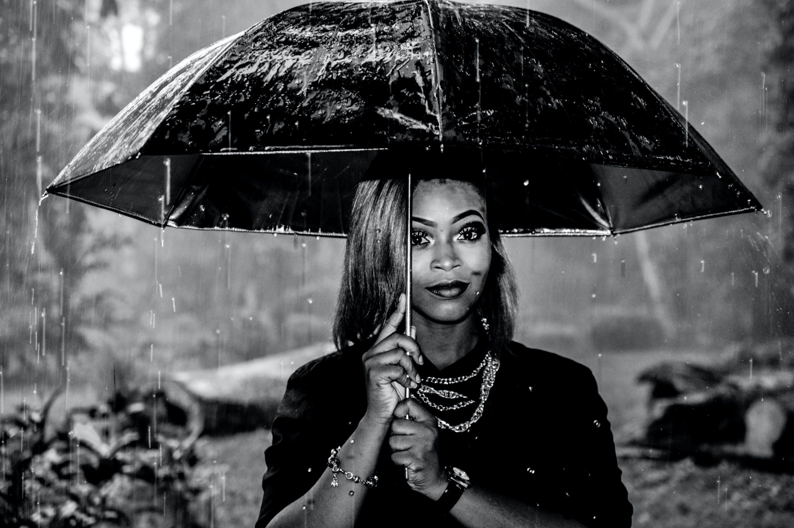Na foto uma mulher com um guarda-chuva na chuva.