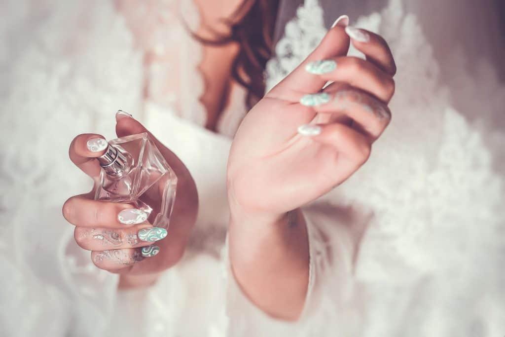 Moça vestida de noiva aplica perfume Chanel nos pulsos.